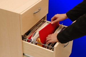 Filing Cabinet - woman putting back an important file into cabinet