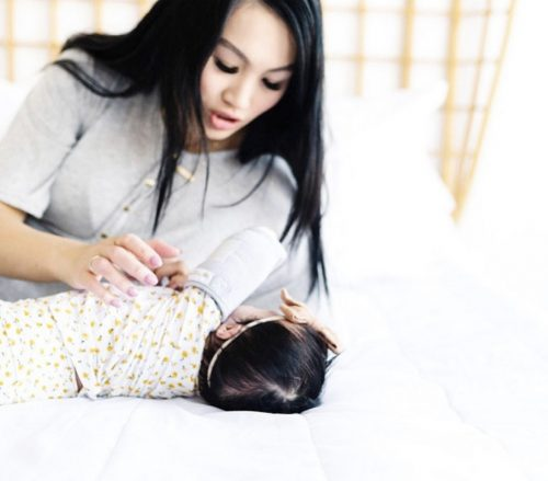 A mother using Swaddle Sleeves on her infant.