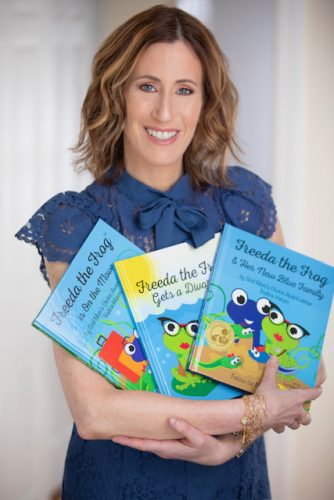 Nadine Haruni and a few of the books from her Freeda the Frog children's book series.