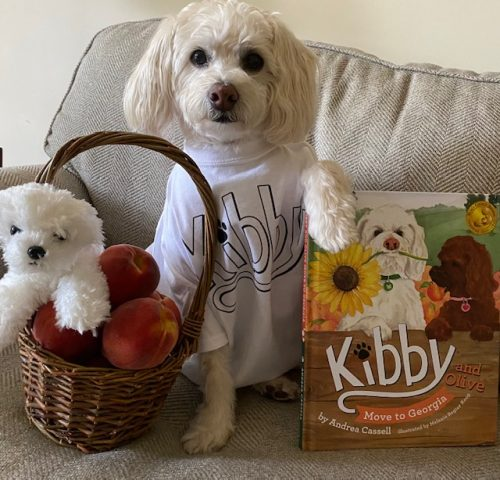 """Kibby posing with his new book, """"Kibby and Olive Move to Georgia"""""""