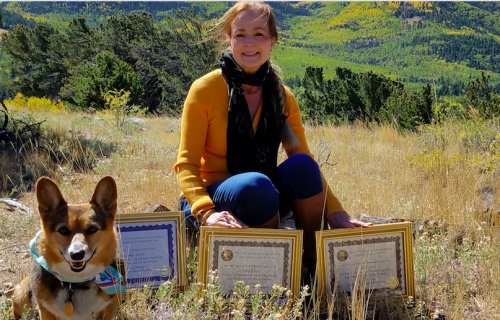 Joni and her corgi Sagebrush with her accolades for her Corky Tails book series.