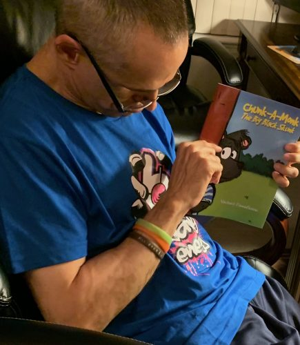 """Mike Passafiume with his book, """"Chunk-A-Monk, The Big Black Skunk"""""""